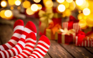 Family in Christmas socks. Mother and baby having fun together. People relaxing at home. Winter holiday Xmas and New Year concept