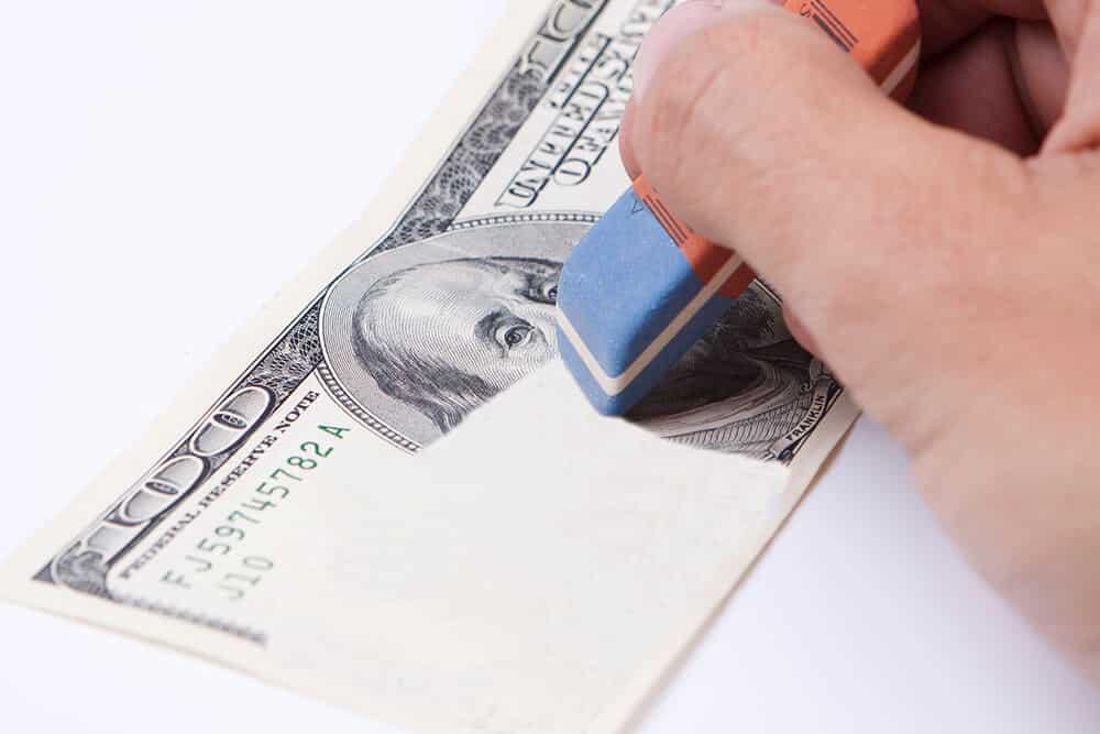 erasing 100 dollar bill with a blue eraser