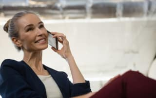 Smiling businesswoman communicating on smart phone at office