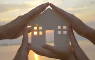 Group of human palms on all sides of a cut out house diagram with setting sun coming through window over water