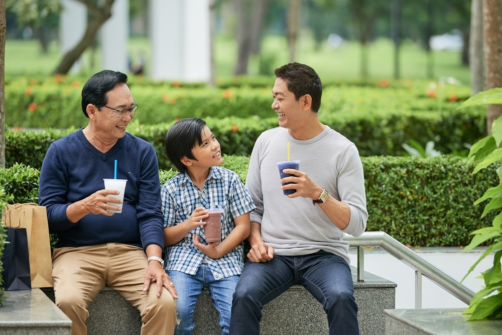 Asian boy smiling and enjoying tasty beverage while sitting between father and grandfather in park