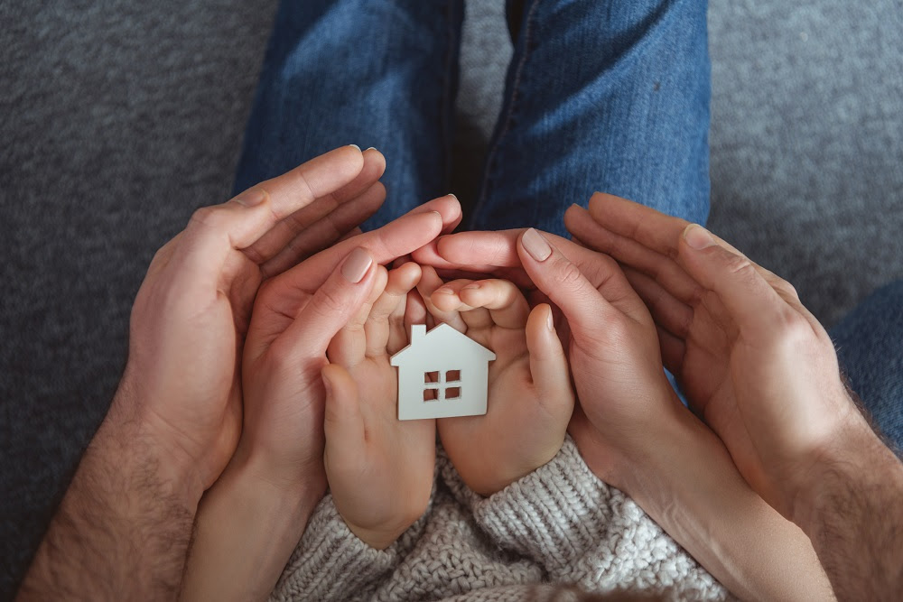 cropped shot of family holding small house model in hands